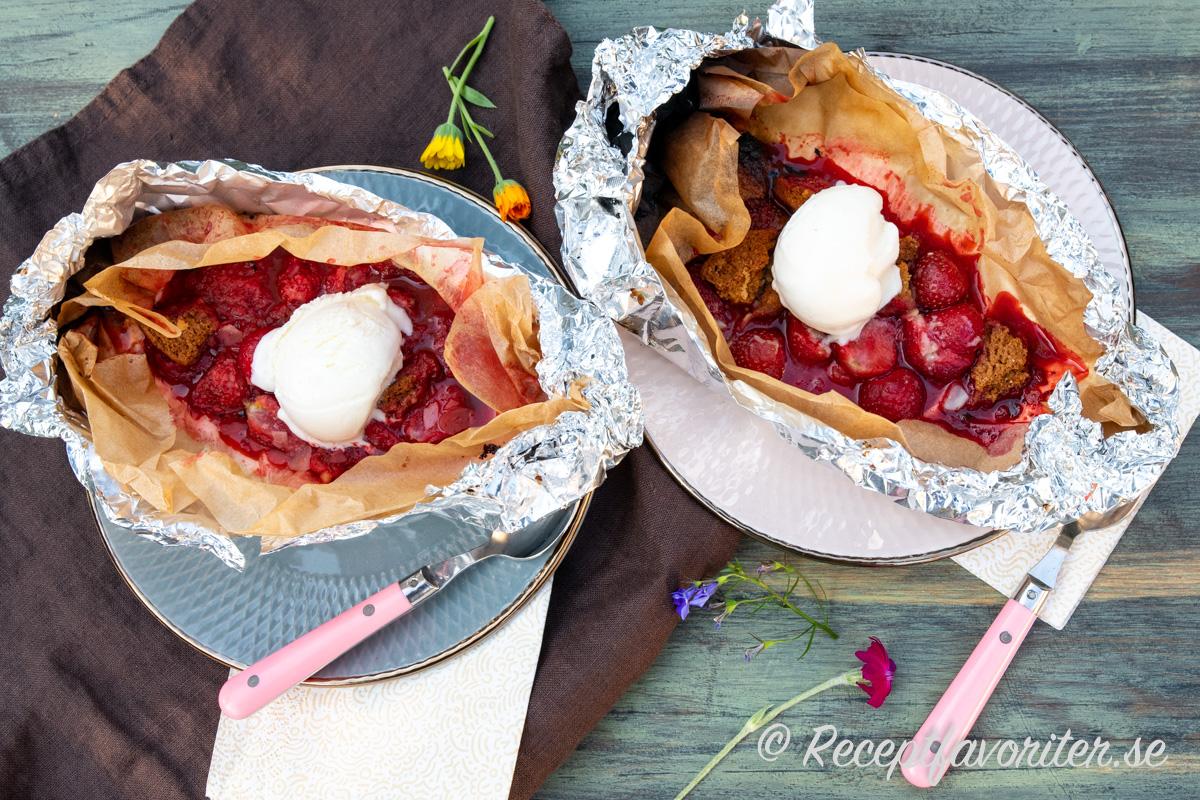 Grilla foliepaket med jordgubbar, vit choklad, kaksmulor, mandelmassa och mandelspån samt servera med vaniljglass.