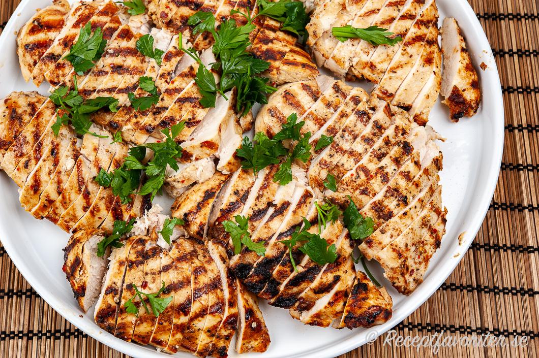 Grillade kycklingfiléer eller kycklingbröst på serveringsfat i skivor med persilja.