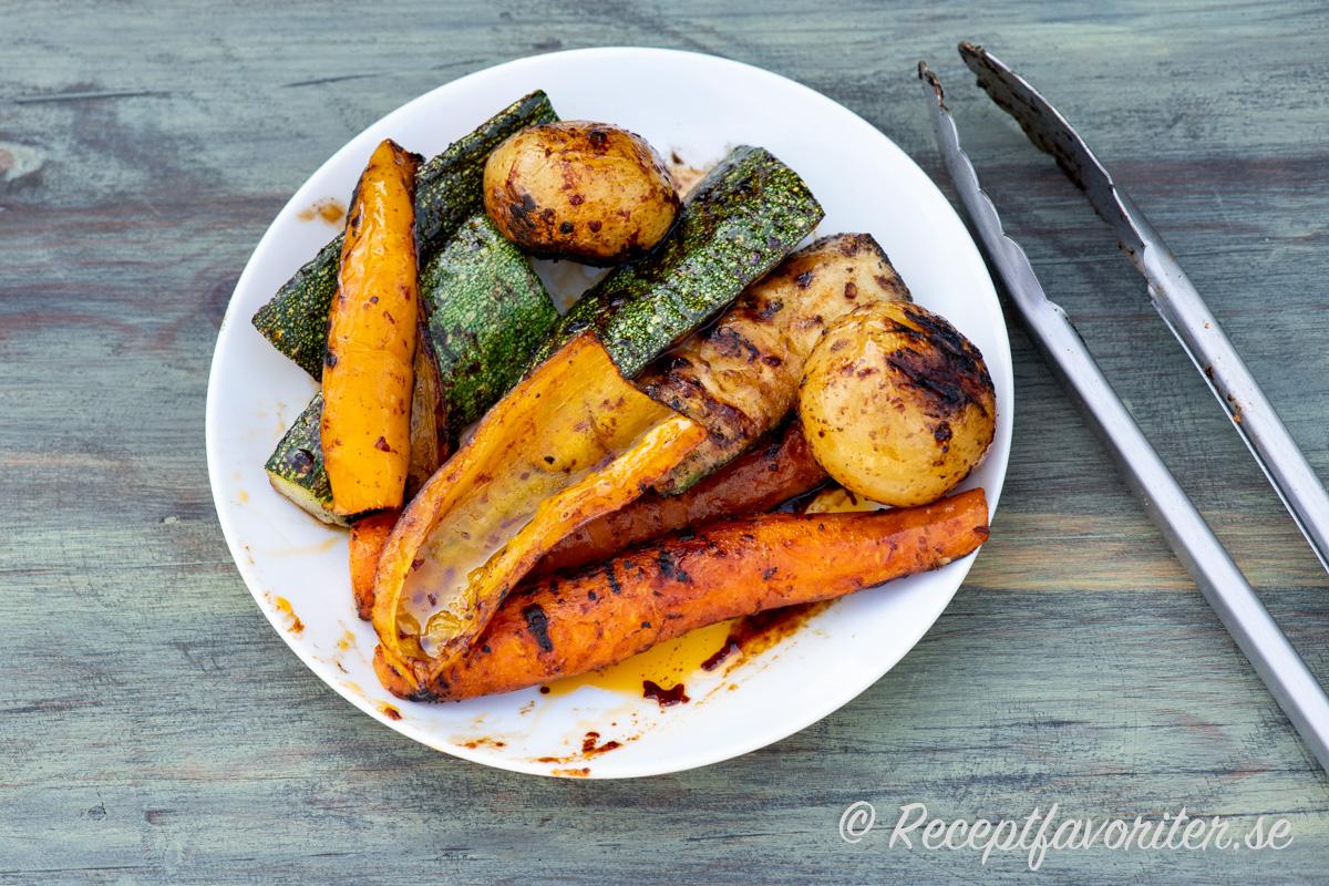 Grillade zucchinis, morötter, paprika och potatis på tallrik.