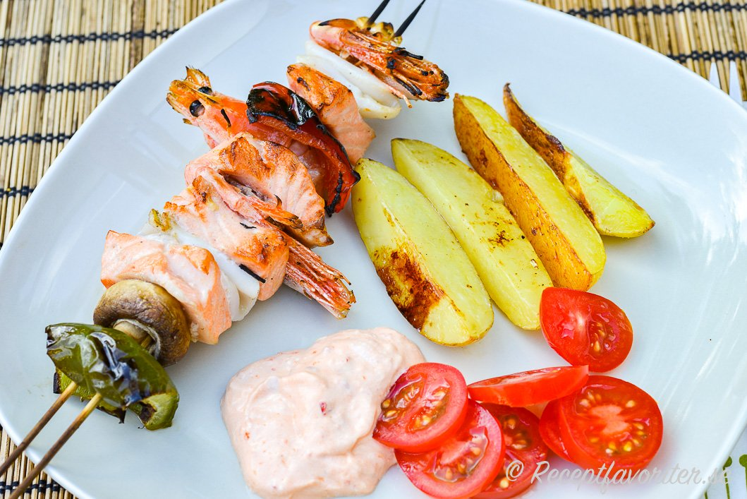 Fiskspett med lax, räkor, paprika, champinjoner och bläckfisk serverat med tillbehör på tallrik.