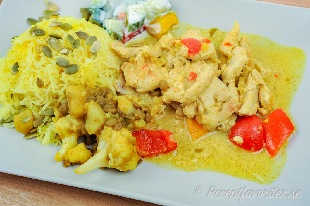 Gryta med kycklingfilé och curry serverad med tillbehör som raita, ris och linser.