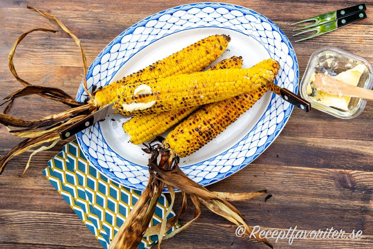Grillad färsk majs med eller utan blast serverad med flingsalt, smör och svartpeppar.
