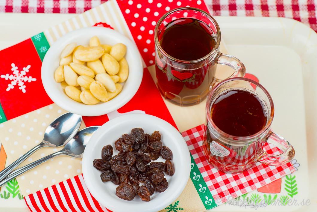 Hemjäst glögg serverad i glögg-glas med skållad mandel och russin