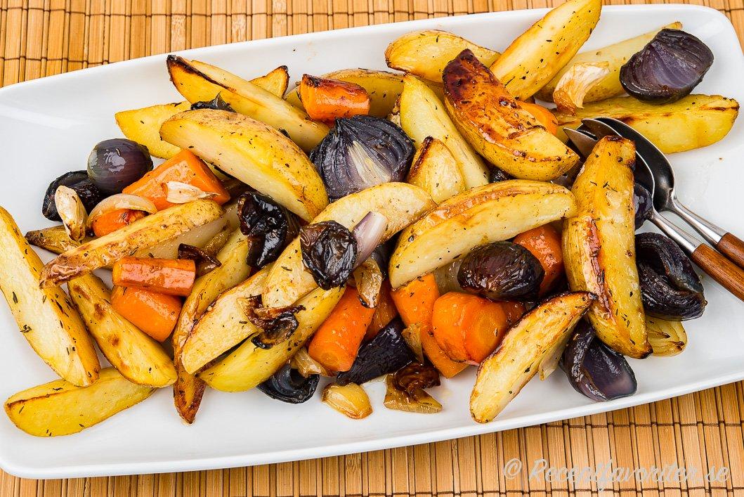 Fina stora klyftpotatisar smaksatta med lite honung och olja tillsammans med rödlök, morot och vitlök på serveringsfat.