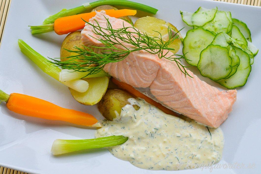 Inkokt laxfilé på tallrik med skarpsås, potatis, knipplök, morot och inlagd gurka.