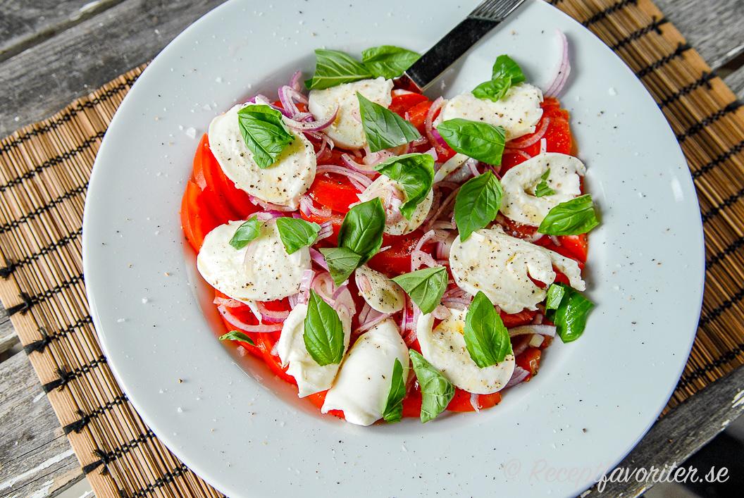 Caprese på fat med tomater, mozzarella, basilika och rödlök