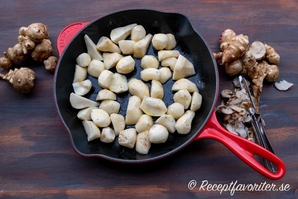 Jordärtsskockorna skalas och blandas med lite rapsolja, salt och peppar innan de tillagas i ugnen.