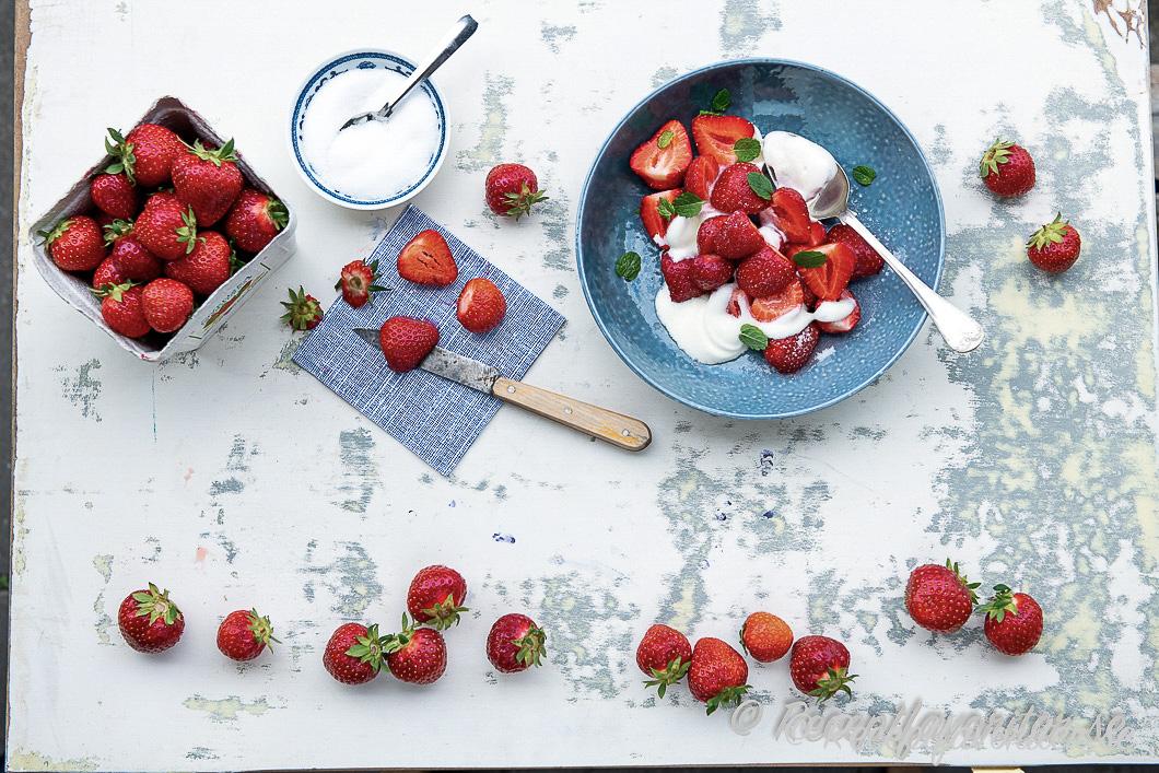 Svenska söta jordgubbar på bricka med grädde och socker