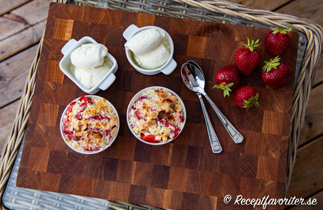 Två portioner jordgubbsgino i formar serverade med vaniljglass.