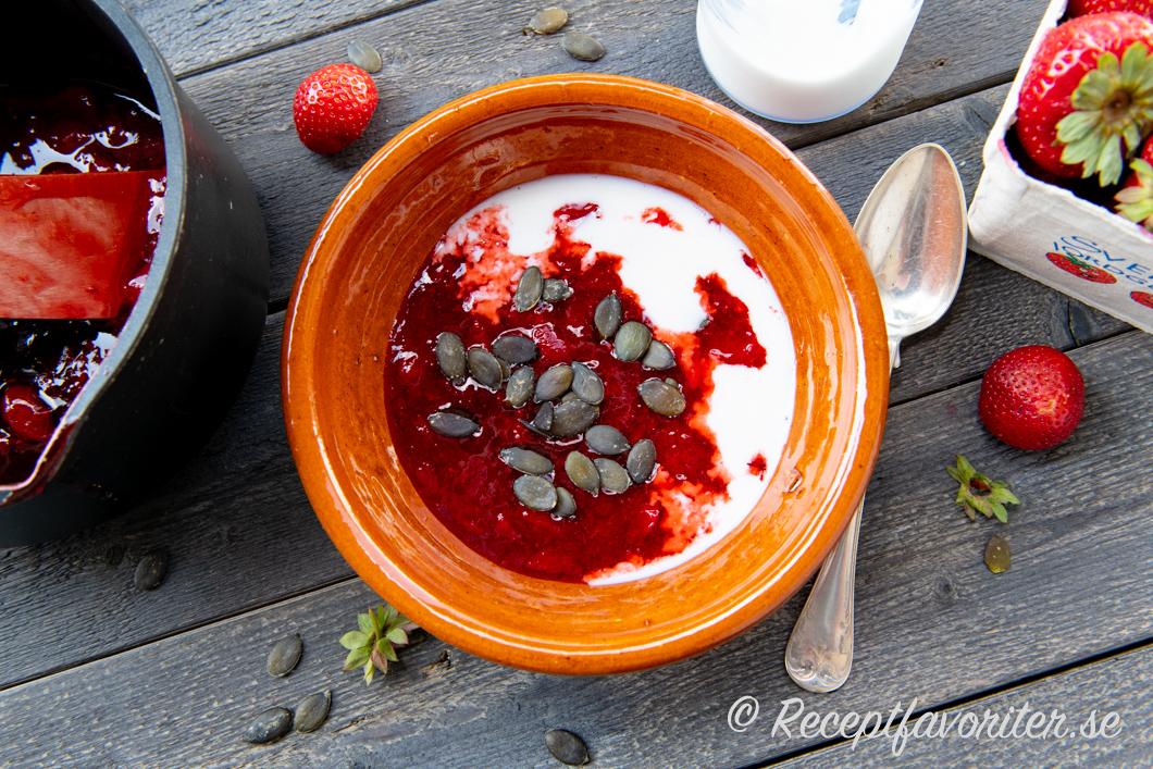 Jordgubbskräm serverad i skål med mjölk och pumpakärnor