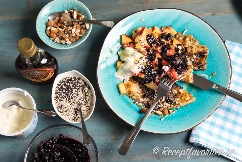 Kalljästa blåbärspannkakor med nötter; tärnad frukt som persika, melon, blåbär, äpple; yoghurt; sesamfrön och lönnsirap.