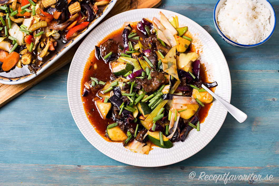 Friterad biff på kinesiskt vis med grönsaker i sötsur sås serverad med ris på tallrik.