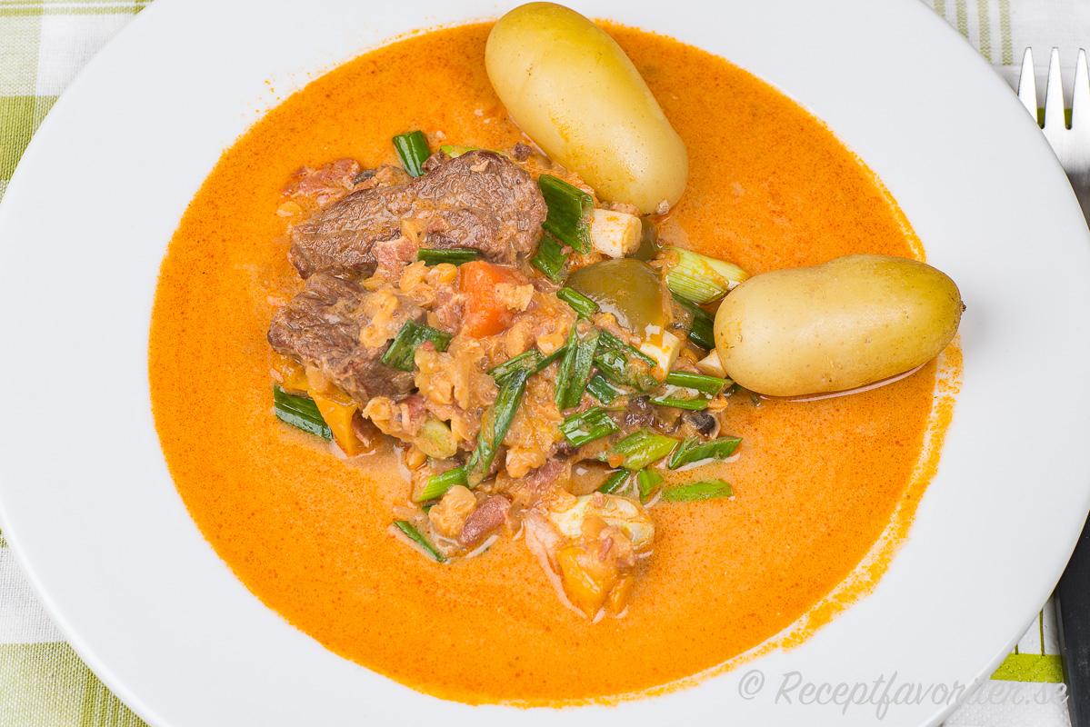 Grytan serverad i djup tallrik med kokt potatis till