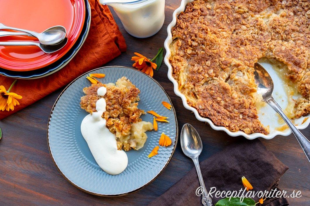 Täcket till äppelpajen görs av smält smör, sirap, rörsocker, havregryn, vetemjöl, salt och bakpulver och stelnar så det blir knäckigt och knaprigt.
