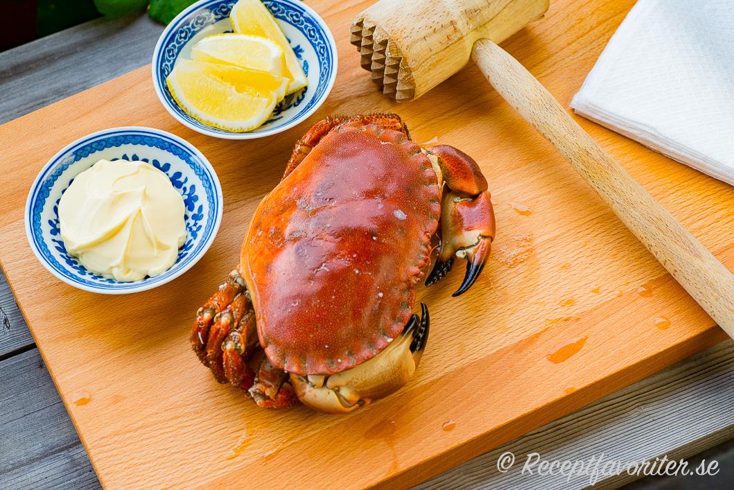 Kokt krabba serverad på skärbräda med träklubba, citron och majonnäs samt servett.