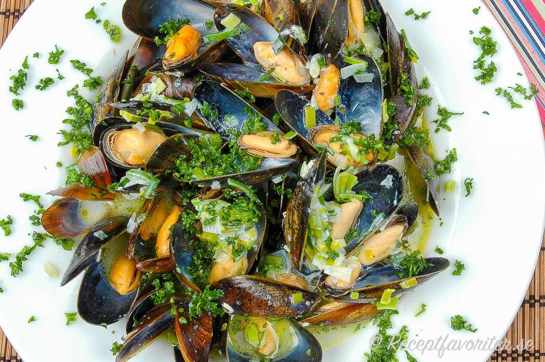 Nykokta musslor med lök och persilja på tallrik