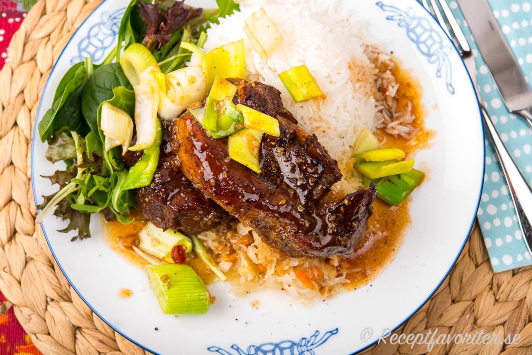 Revbensspjällen serverade med ris, kimchi och sallad på tallrik.