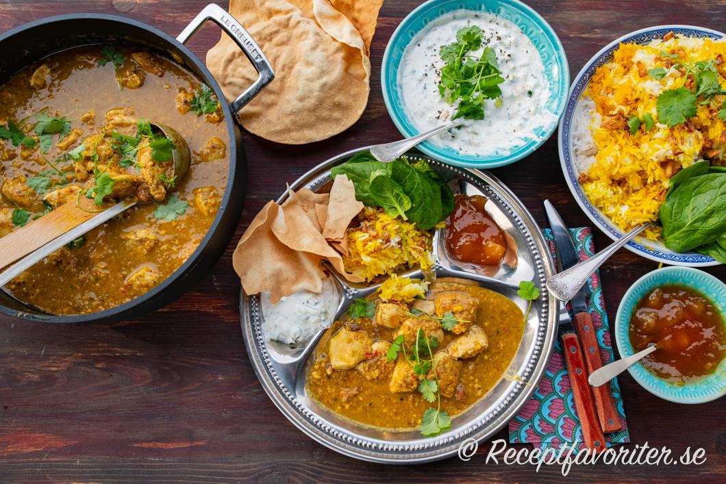 Kyckling Korma serverad med raita, ris, papadams och mango chutney.