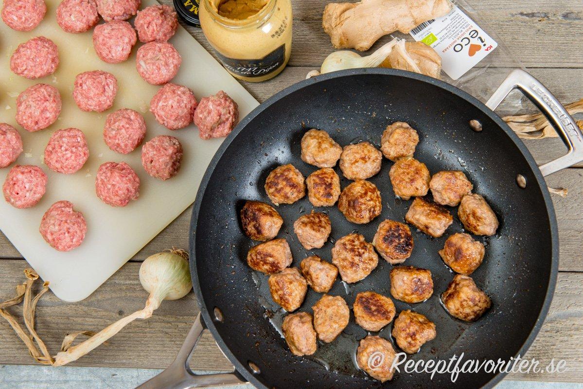 Köttbullarna i stekpanna omgiven av ingredienser som Dijonsenap, lök samt färsk ingefära.