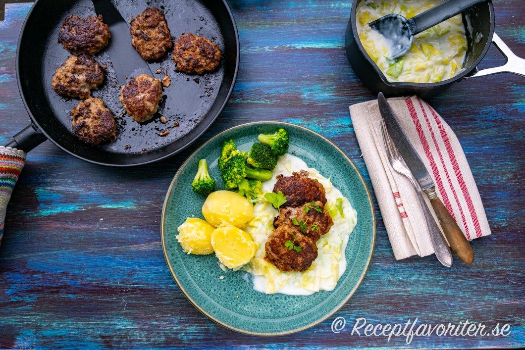 Köttfärsbiffar med stuvad vitkål, kokt potatis och broccoli på tallrik.