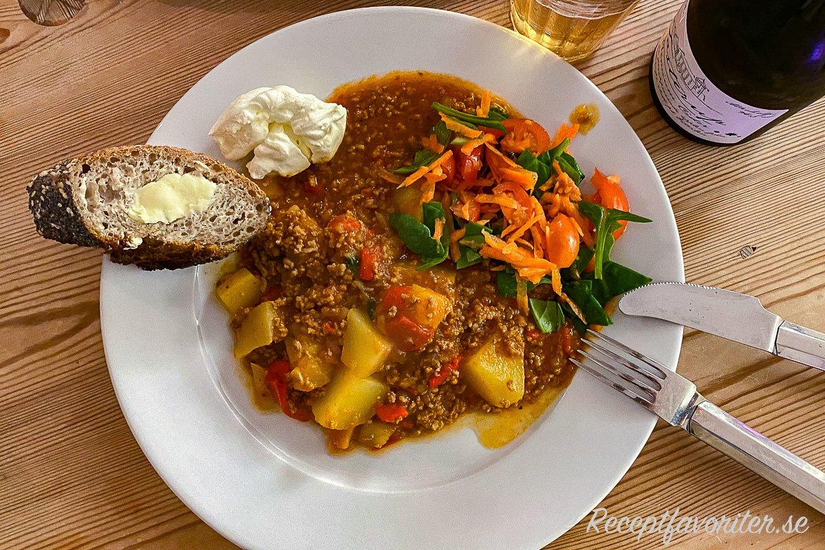 Köttfärsgrytan serverad med tillbehör - surdegsbaguette med smör, crème fraiche, sallad med hackad babyspenat, tomat och riven morot samt en torr cider från Tosterup.