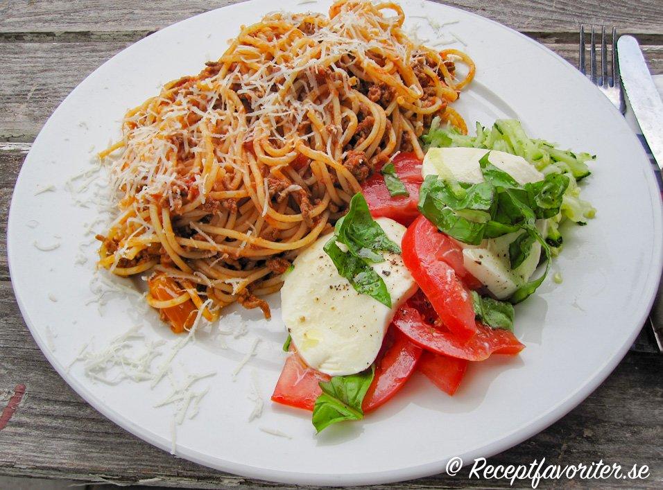 Köttfärssås med spagetti på tallrik med tomat och mozzarellasallad