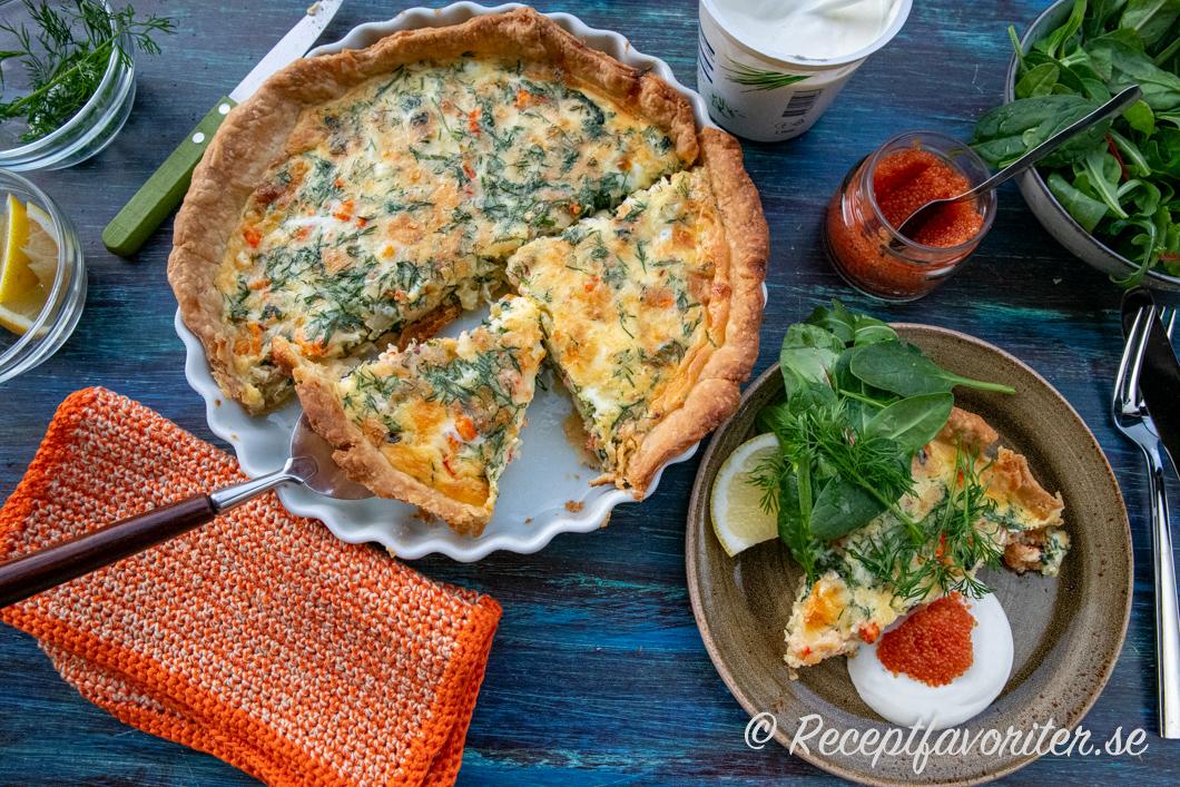 Kräftpaj serverad med tillbehör som gräddfil, rom och grönsallad.