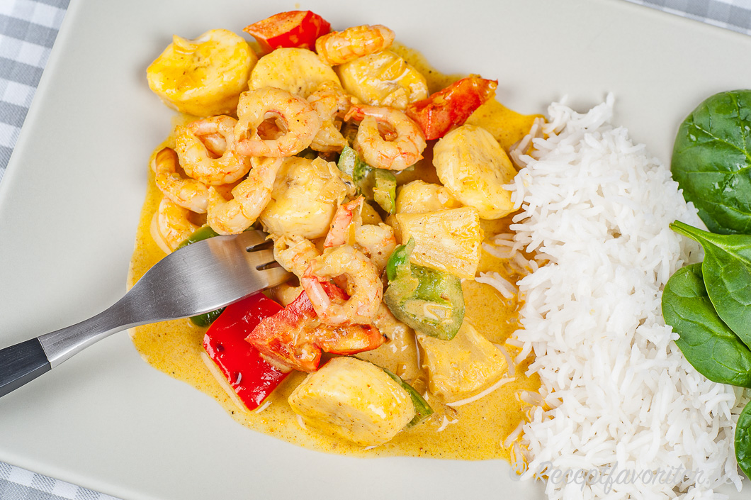 Räkor med paprika, ananas, banan i krämig sås på kreolskt vis serverad på tallrik med ris och babyspenat.