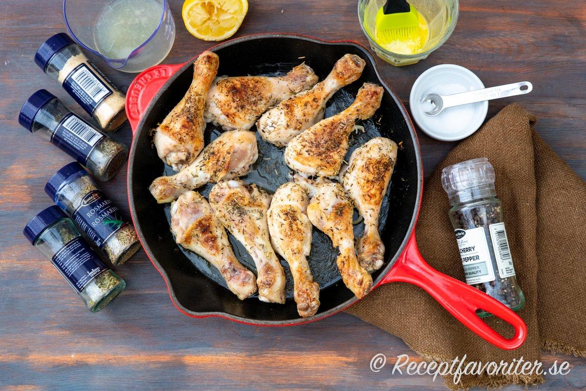 Kycklingben får god smak i ugnen av smält smör, citronjuice, rosmarin, vitlök, timjan, oregano och svartpeppar.