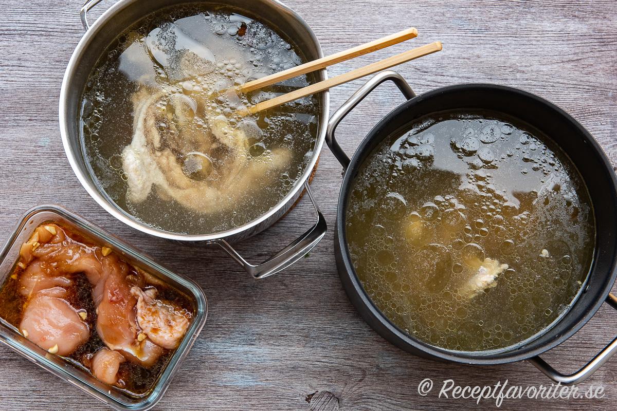 Två kastruller kycklingbuljong till ramen med kycklingköttet urplockat vid sidan.