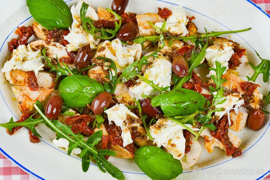 En slags kycklingsallad med soltorkad tomat, ruccola, färsk basilika och mozzarella samt oliver.