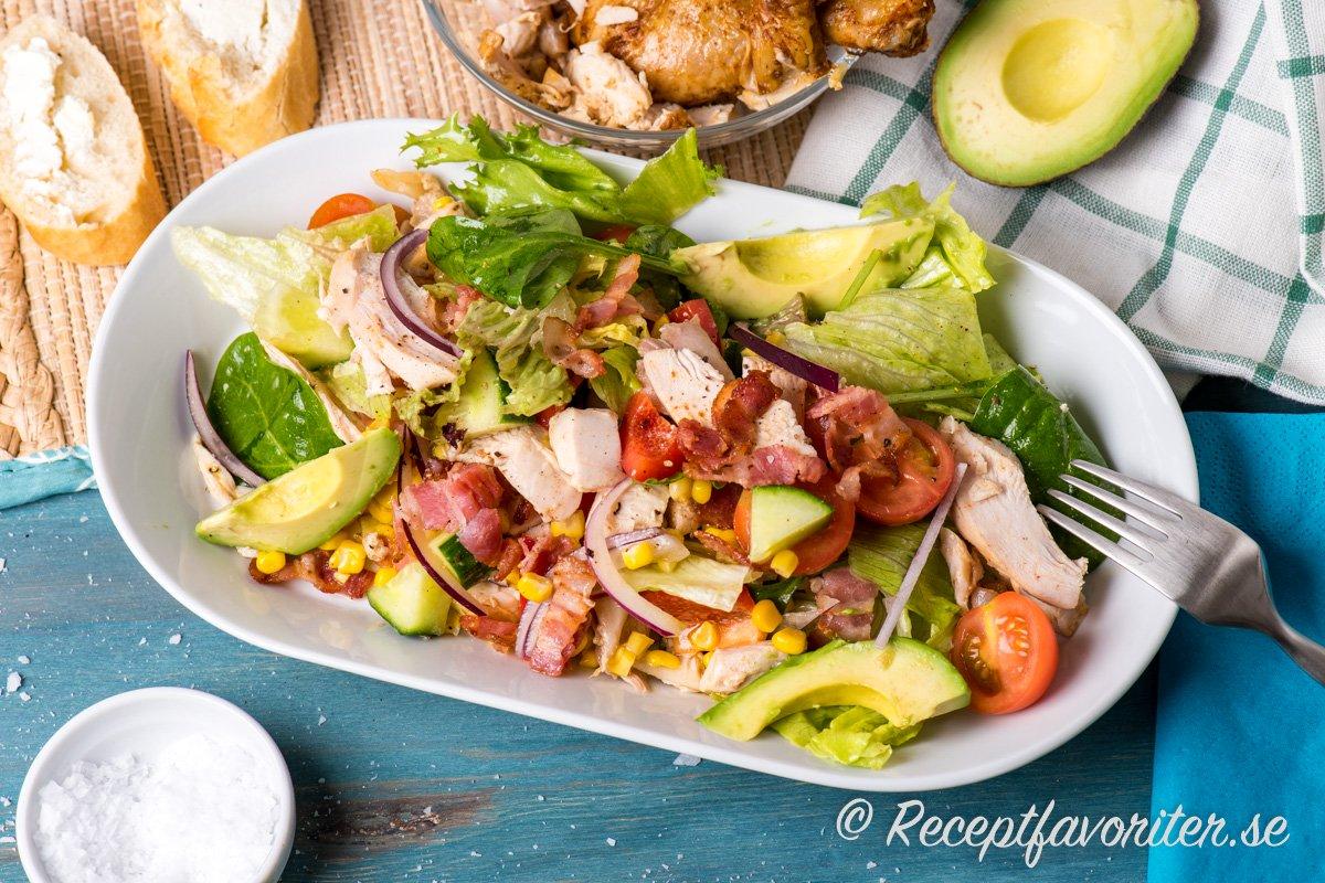Sallad med grillad kyckling i bitar samt avokado, bacon, grönsallad, dressing och annat gott.