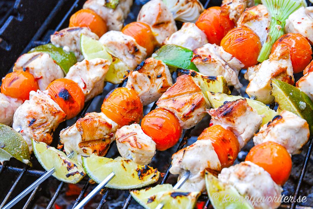 Grillspett med kycklingfilé, färsk lime, knipplök och cocktailtomater på grillen.