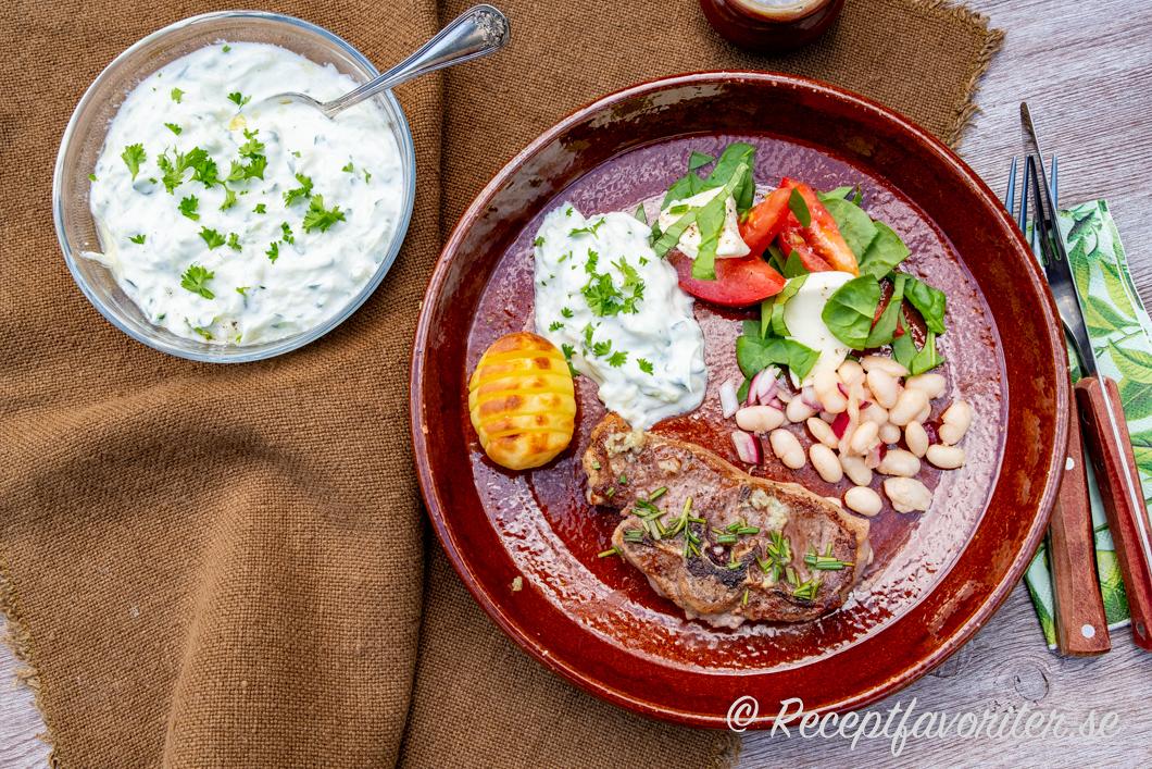 Zucchinzikin serverad med grillad lammkotlett, rostad färskpotatis hasselbacksstil; tomatsallad med mozzarella och basilika; marinerade vita bönor med rödlök.