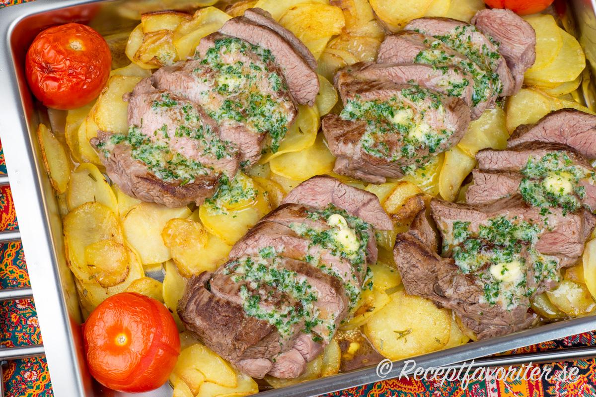 Lammrostbiff med vitlökssmör på en bädd av skivad rostad råstekt potatis och bakade tomathalvor.