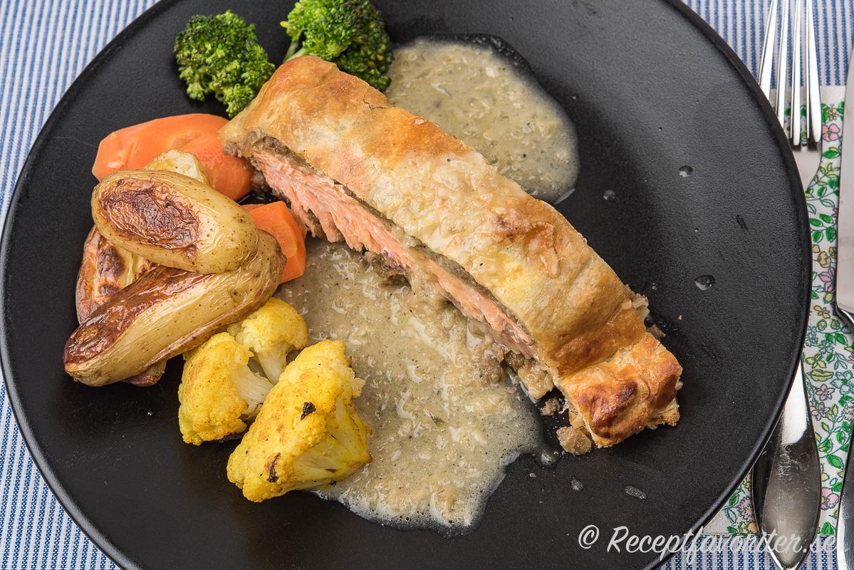 Lax Wellington serverad med en smörsås, rostad potatis och blomkål samt kokt morot och broccoli.