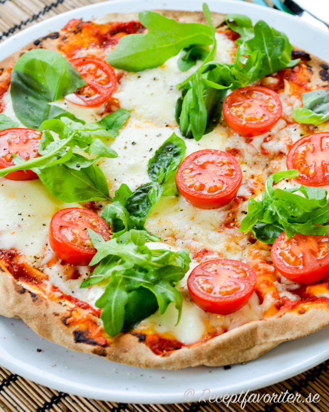 Pizza av Libabröd - arabiskt tunnbröd - toppad med mozzarella, cocktailtomater och ruccola samt basilika.