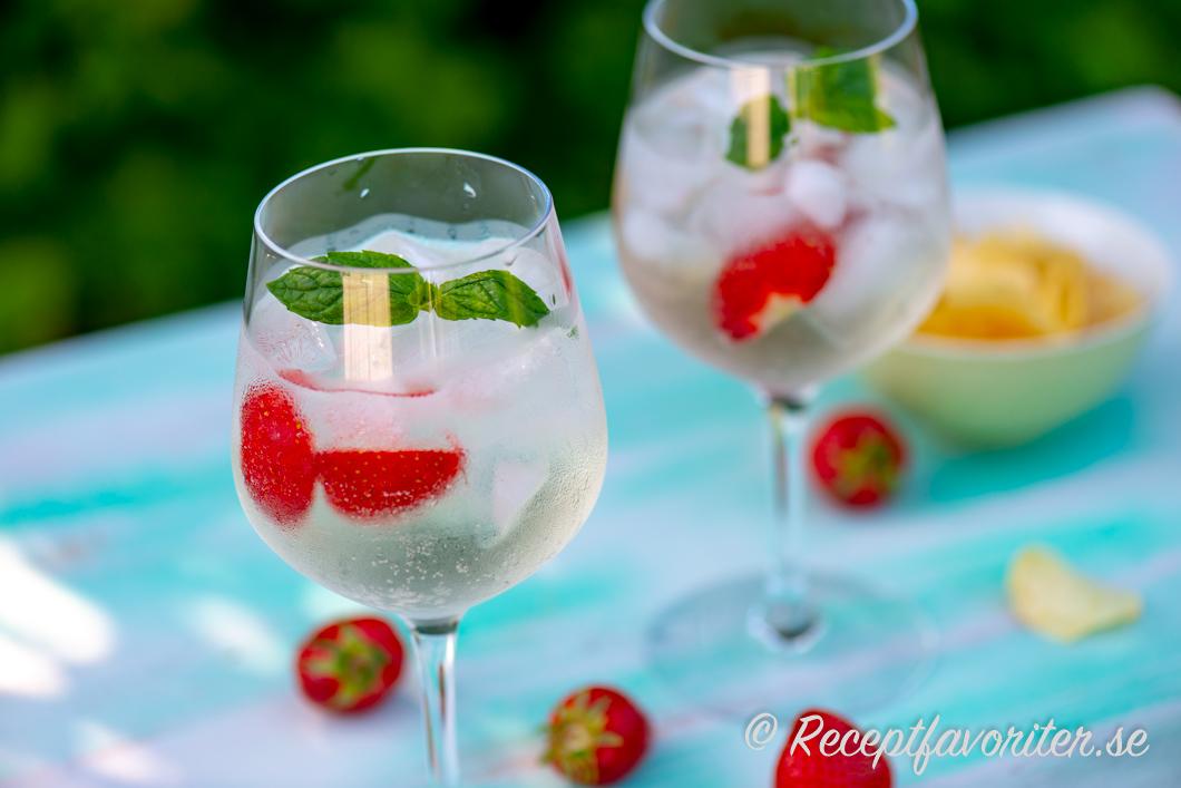 En cocktail eller drink med Lillet Blanc, tonic water, is, jordgubbar och mynta.