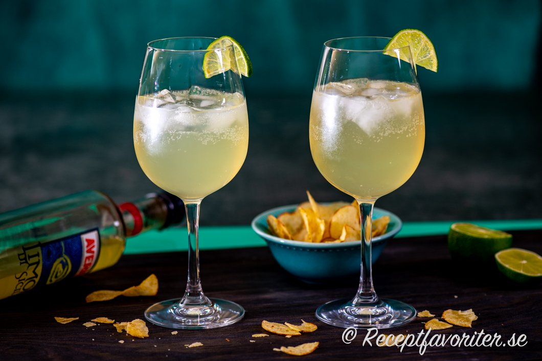 Limoncello Spritzer serverade i två glas med is och limeklyfta samt chips.