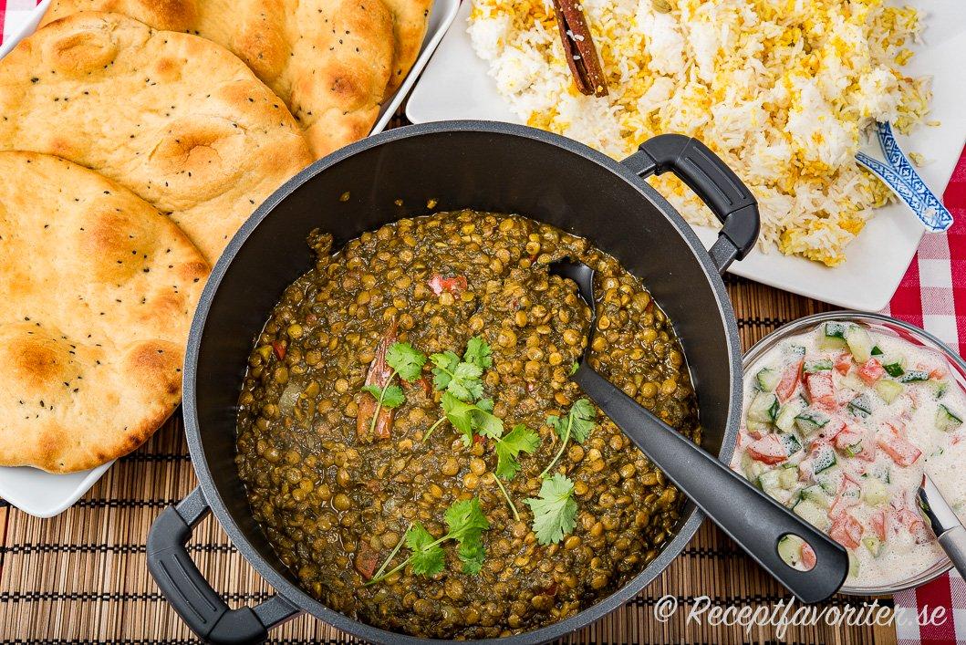 Linsgrytan serverad med förslag på tillbehör som naan-bröd; vegansk raita och basmatiris kokt med kanel, hel kardemumma samt gurkmeja.