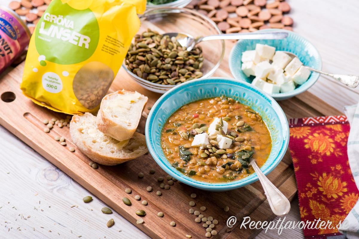 En matig soppa med gröna linser, tomat och spenat toppad med pumpafrön och tärnad paneer indisk ost.