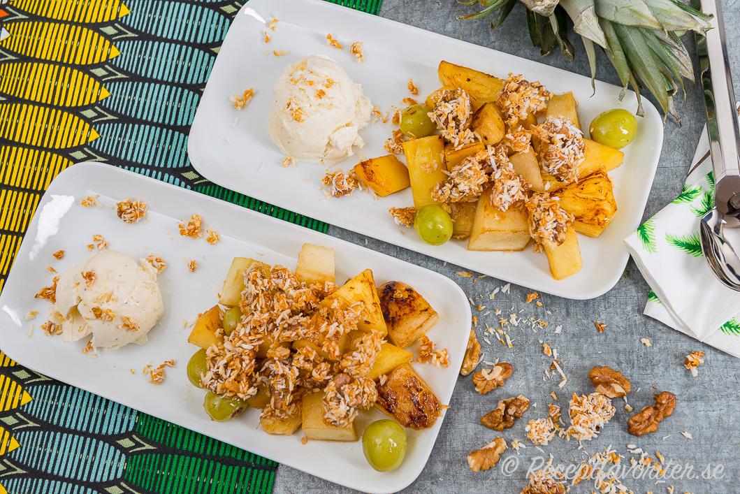 Ljummen fruktsallad på tallrik med valnötter och kokos samt glass