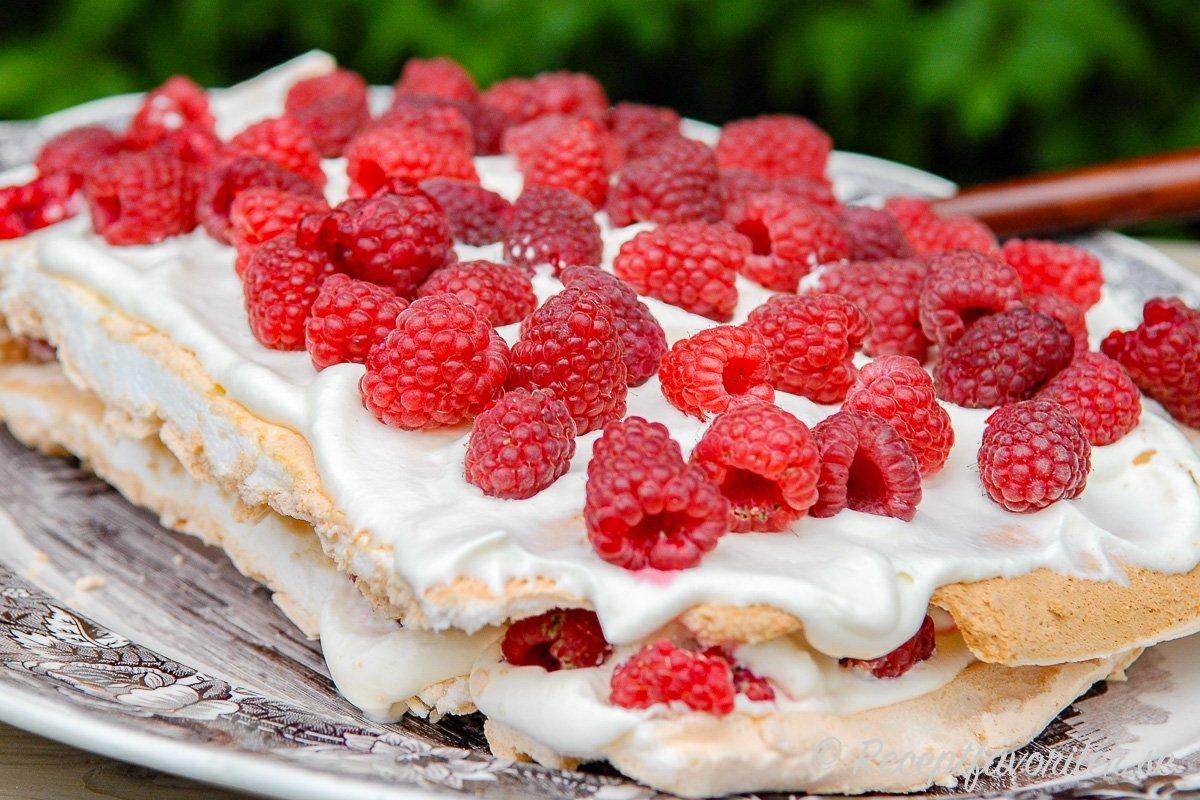 Marängtårta med vispad grädde och färska hallon blir en passande dessert efter kräftorna.