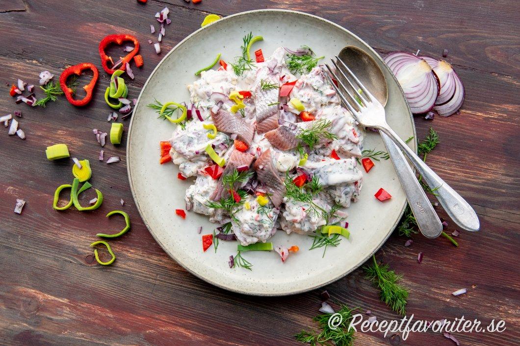 Matjessallad på tallrik med garnering