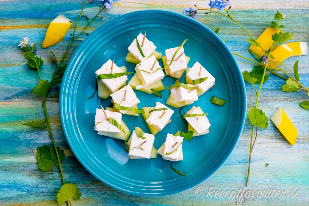 Aptitretande tilltugg med salt fetaost och söt melon på tandpetare på fat