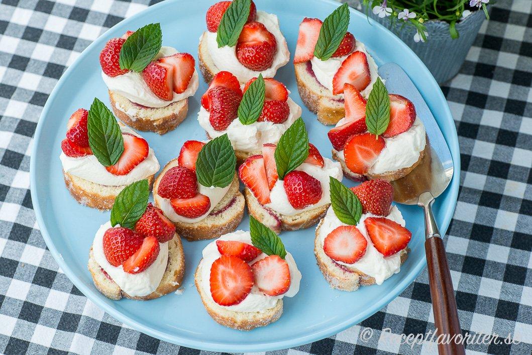 Små bakelser av rulltårta, grädde och jordgubbar som passar till sommarens fester och kalas som midsommar med mera.