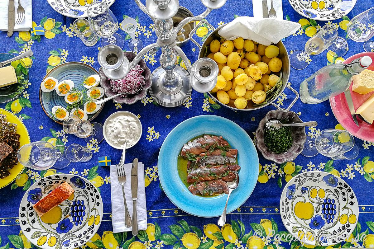 Ett bord dukat till midsommarlunch med knäckebröd, frökex och kavringkex; smör; kokt ägg; stekt lax för de som ej vill ha sill; hackad rödlök, gräddfil, matjessill, gräslök, färskpotatis samt utanför bild lagrad ost, snaps och öl.