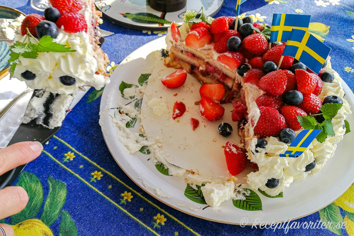 Midsommartårtan toppad med färska jordgubbar och blåbär samt citronmeliss och svenska flaggor.