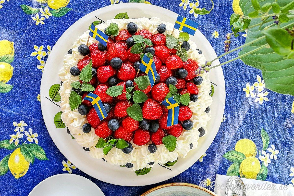 Midsommartårta på midsommarbordet med svenska flaggor och extra blåbär samt citronmeliss.