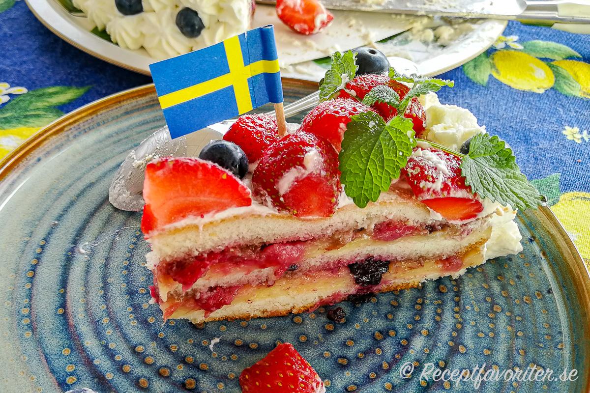 En bit midsommartårta med färska jordgubbar och blåbär och massor av god fyllning av vaniljkräm och mosade bär.